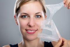 Kvinna som av skalar en ansikts- maskering royaltyfri bild