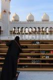 Kvinna som av tar hennes skor, innan att skriva in Sheikh Zayed Grand Mosque Royaltyfri Fotografi