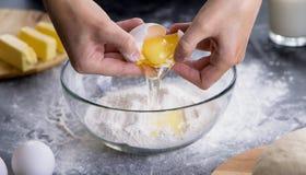 Kvinna som avskiljer äggulan från äggvitan Arkivfoton