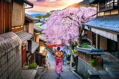 Kvinna som bär den japanska traditionella kimonot som går på det historiska Higashiyama området i våren, Kyoto i Japan royaltyfria foton