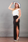 Kvinna som bär den långa svarta vita klänning- och solhatten Arkivbild