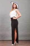 Kvinna som bär den långa svarta vita klänning- och solhatten Arkivbilder