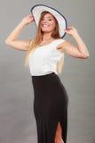 Kvinna som bär den långa svarta vita klänning- och solhatten Royaltyfria Bilder