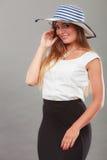 Kvinna som bär den långa svarta vita klänning- och solhatten Royaltyfri Foto