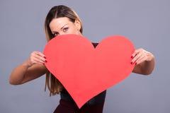 Kvinna som bär den röda klänningen som rymmer stort symbol för hjärtateckenförälskelse Arkivfoton