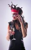 Kvinna som bär den röda maskeringen på maskeradpartiet som dricker champagne fotografering för bildbyråer