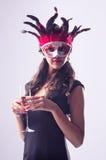 Kvinna som bär den röda maskeringen på maskeradpartiet som dricker champagne royaltyfria foton