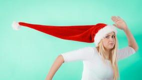 Kvinna som bär den windblown långa jultomtenhatten royaltyfria foton