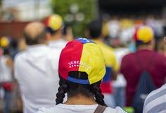 Kvinna som bär det venezuelanska flaggalocket på protesten royaltyfria foton