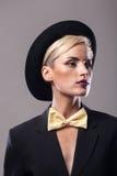 Kvinna som bär en dräkt och en hatt Royaltyfria Bilder
