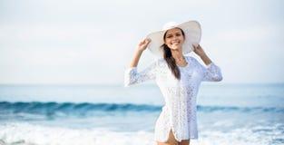 Kvinna som bär en hatt och le för sugrör royaltyfri bild