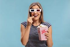 Kvinna som bär ett par av exponeringsglas 3D och äter popcorn Royaltyfri Foto