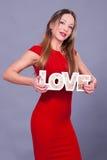 Kvinna som bär för teckenförälskelse för röd klänning hållande symbol Arkivfoton