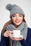 Kvinna som bär i halsduk- och hattinnehavkopp med kaffe Arkivfoton