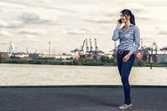 Kvinna som bär mager jeans, medan tala på telefonen Fotografering för Bildbyråer