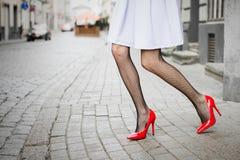 Kvinna som bär röda skor för hög häl i stad Royaltyfria Bilder