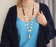 Kvinna som bär stilfulla halsband med skal royaltyfri bild