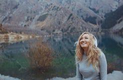 Kvinna som bär trådlös hörlurar på sjön royaltyfria bilder