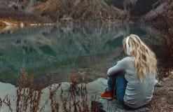 Kvinna som bär trådlös hörlurar på sjön fotografering för bildbyråer
