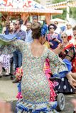 Kvinna som bär traditionella Sevillana klänningar och dansar en Sevillana på Sevillen April Fair Royaltyfri Bild