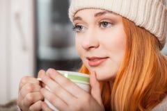 Kvinna som bär varma kläder och dricker den varma drinken Royaltyfri Fotografi