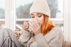 Kvinna som bär varma kläder och dricker den varma drinken Royaltyfria Foton
