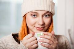 Kvinna som bär varma kläder och dricker den varma drinken Arkivfoto