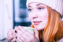 Kvinna som bär varma kläder och dricker den varma drinken Royaltyfri Bild