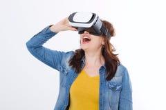 Kvinna som bär VR-hörlurar med mikrofon och ser upp i virtuell verklighetisolat på vit bakgrund white för teknologi för bärbar da royaltyfri foto