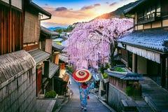 Kvinna som b?r den japanska traditionella kimonot som g?r p? det historiska Higashiyama omr?det i v?ren, Kyoto i Japan royaltyfria bilder