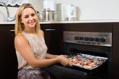 Kvinna som bakar hemlagad pizza Arkivfoto
