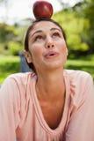 Kvinna som balanserar ett äpple på henne som är head Arkivfoton