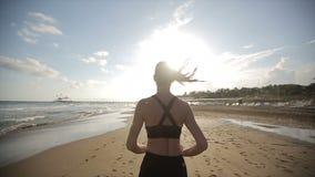 Kvinna som bara kör på den härliga solnedgången på stranden långsam rörelse lager videofilmer