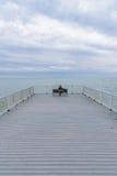 Kvinna som bara sitter på bänken som ser Lake Michigan arkivfoto