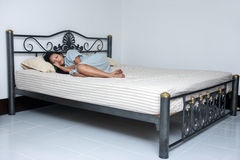 Kvinna som bara sover i den stora sängen Royaltyfria Bilder