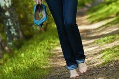 Kvinna som barfota går på gräs Arkivbild