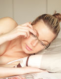 Kvinna som begränsas till liggande avläsning för underlag Arkivbild