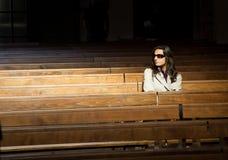 Kvinna som ber i kyrka royaltyfria bilder