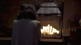 Kvinna som ber i kyrka med stearinljusbakgrund stock video