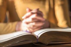 Kvinna som ber med hennes händer över bibeln, hårt ljus royaltyfria bilder