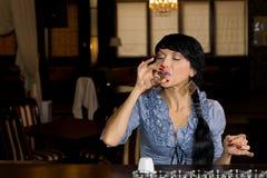 Kvinna som besegrar ett exponeringsglas av proper vodka royaltyfri fotografi