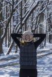 Kvinna som beskådar skogen i vinterdag Arkivbild