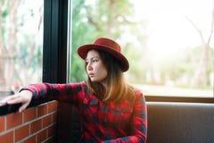 Kvinna som beskådas till och med fönster av coffee shop royaltyfri fotografi