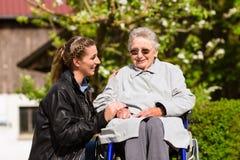 Kvinna som besöker farmodern i vårdhem Arkivbilder