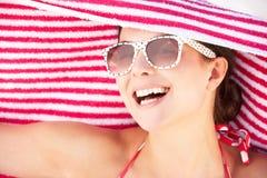 Kvinna som beskyddar från Sun på strandferie Arkivfoto