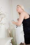 Kvinna som besprutar hennes hår med hårspray Royaltyfri Bild