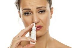 Kvinna som besprutar nasala droppar Arkivfoton