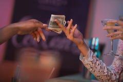 Kvinna som betalar bartendern för coctailar Royaltyfri Fotografi