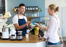 Kvinna som betalar för kaffe Arkivbilder