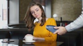 Kvinna som betalar kaféräkningen med kreditkorten till och med STIFTblocket, kontakt mindre betalning stock video